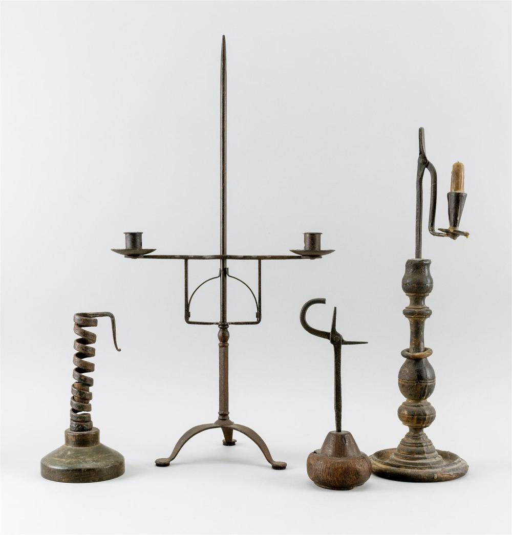 FOUR EARLY WROUGHT IRON AND WOODEN LIGHTING DEVICES 1) Combination rush holder with a turned wooden base. Height 18.5
