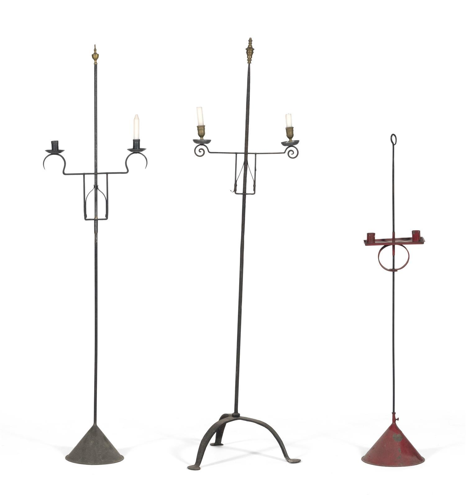 """THREE ADJUSTABLE IRON AND TIN CANDLESTANDS One painted red, height 45"""", and two with turned brass finials, heights 57.5"""" and 58""""."""