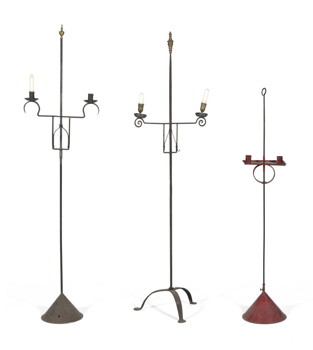 THREE ADJUSTABLE IRON AND TIN CANDLESTANDS One painted red, height 45