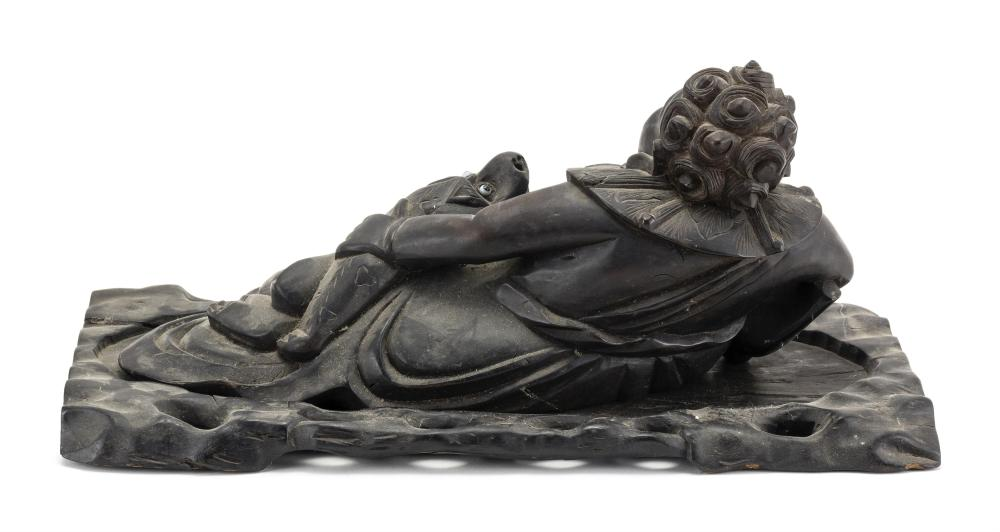 CHINESE CARVED WOOD FIGURE OF LIU HAI In reclining position and accompanied by a three-legged frog. On a carved wood stand. Total le...