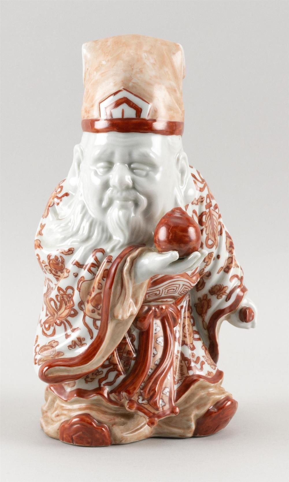"""CHINESE PORCELAIN FIGURE OF SHOU-LAO In orange and white robes and holding a peach and a scepter. Height 11""""."""