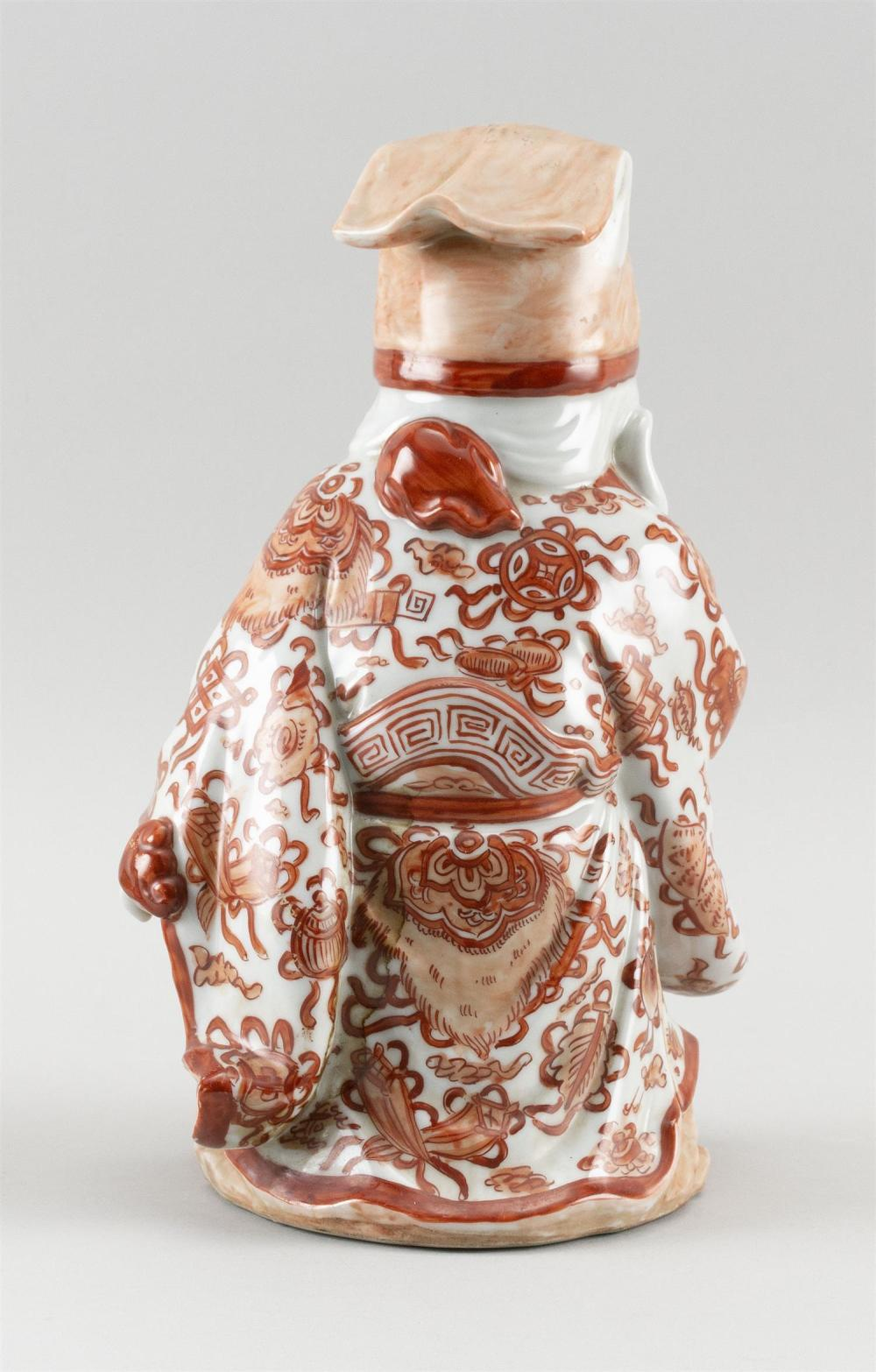 CHINESE PORCELAIN FIGURE OF SHOU-LAO In orange and white robes and holding a peach and a scepter. Height 11