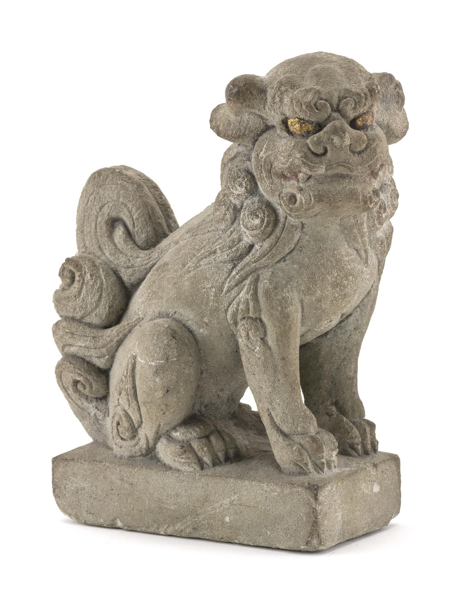 """CHINESE SANDSTONE FIGURE OF A FU DOG Seated on a rectangular plinth. Traces of gilding to eyes. Height 7.5"""". Length 3"""". Width 5""""."""