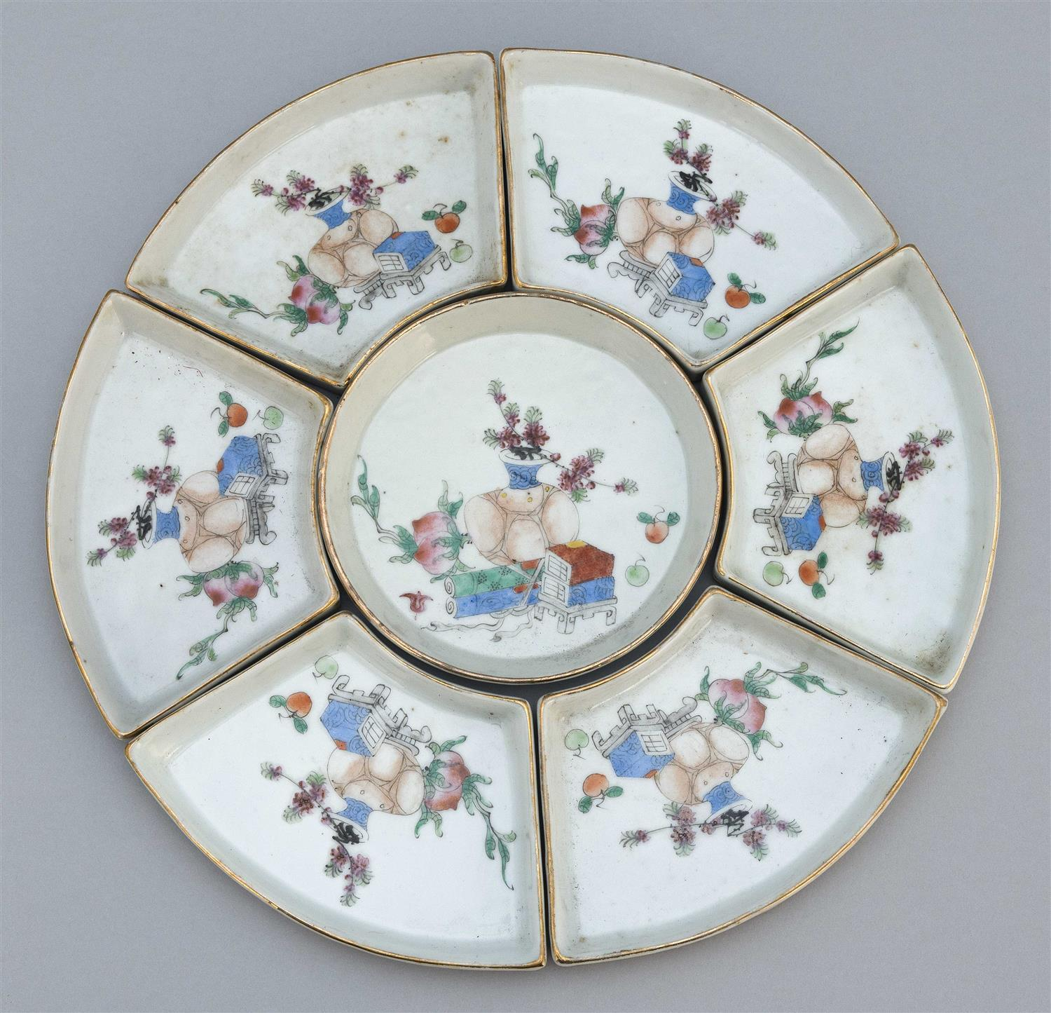 CHINESE FAMILLE ROSE PORCELAIN SEVEN-PIECE SWEETMEAT SET Each condiment tray with gilt rims and decoration of scholars' items. Assem..