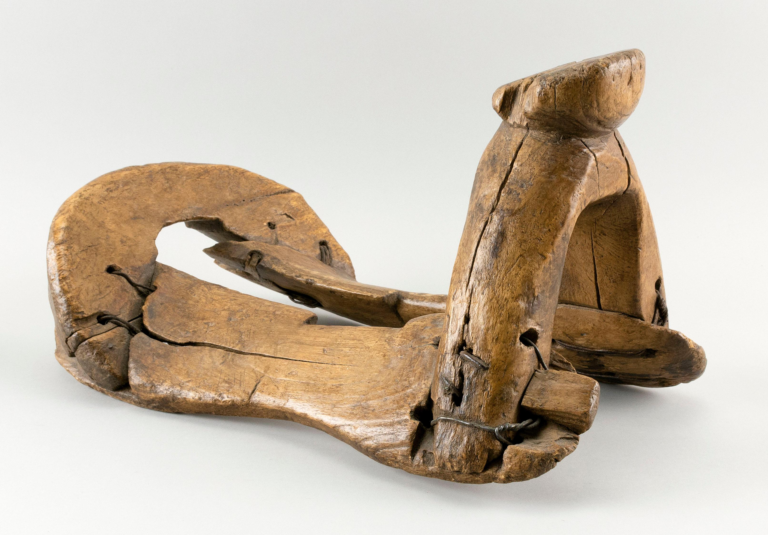 """CHINESE WOODEN SADDLE With iron bindings. Height 12"""". Length 18""""."""