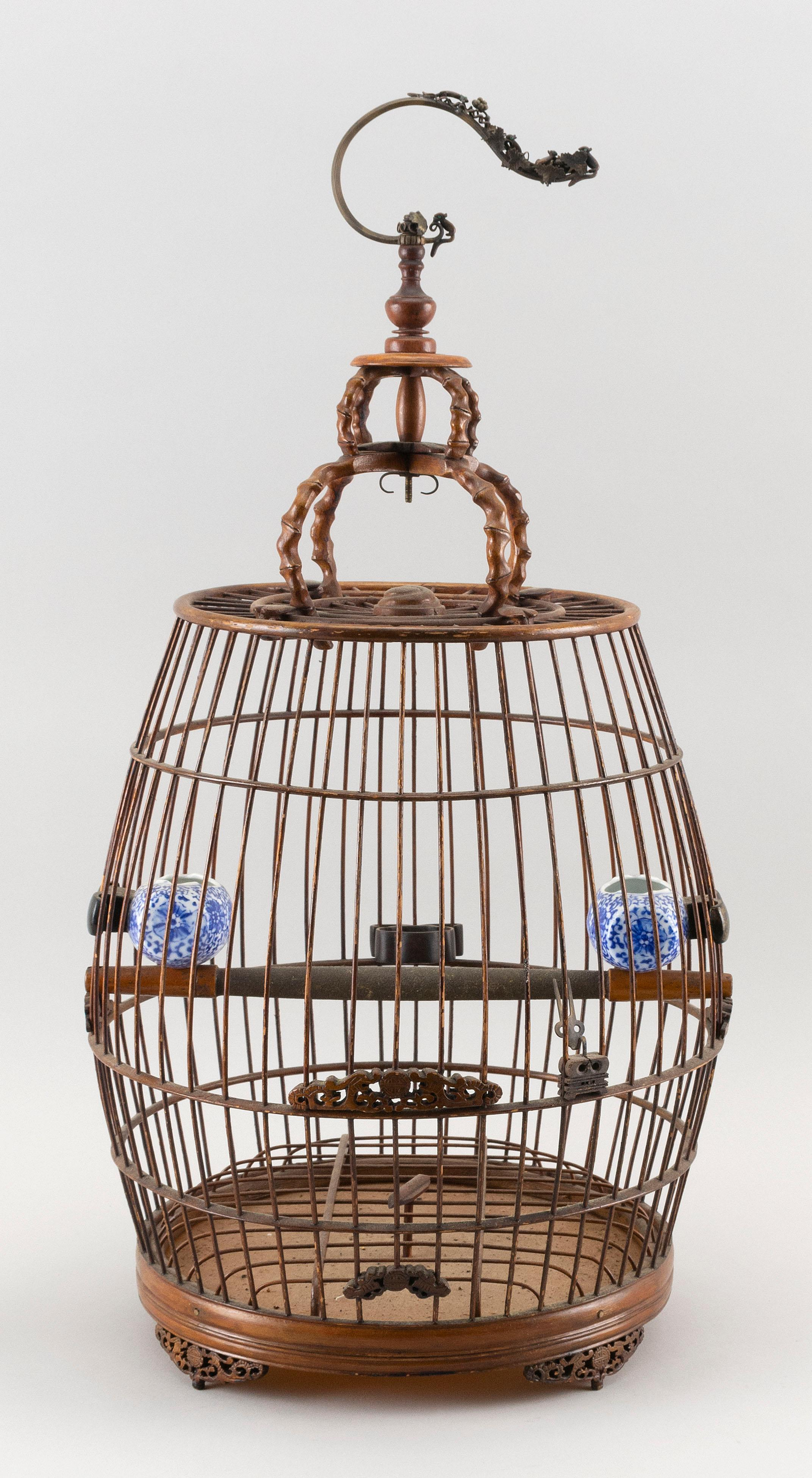 CHINESE BAMBOO BIRDCAGE Cage with plaques and feet carved with a qilin and shou design, and two blue and white porcelain feeders. Ho...