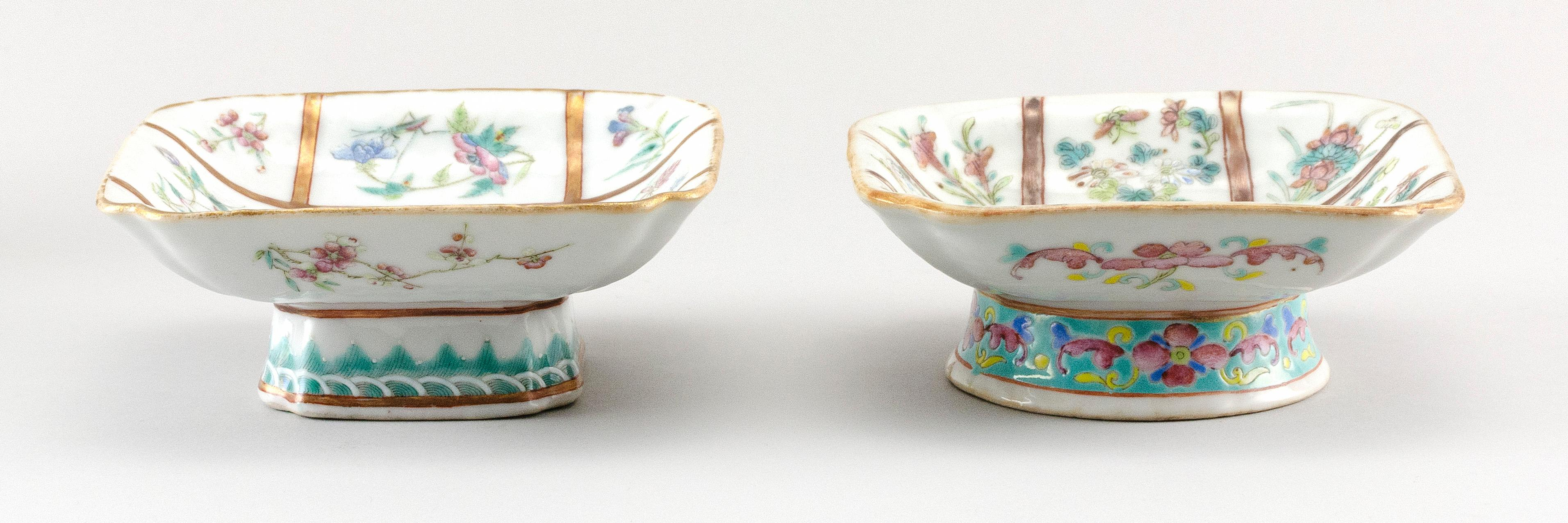 TWO NEAR-MATCHING CHINESE FAMILLE ROSE PORCELAIN FOOTED DISHES Square, with interior decoration of flowers and insects on a bisected...