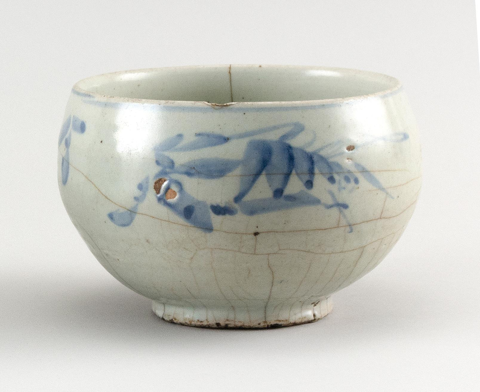 "KOREAN UNDERGLAZE BLUE AND WHITE PORCELAIN BOWL Blue floral sprays about the exterior. Height 4"". Diameter 5.5""."