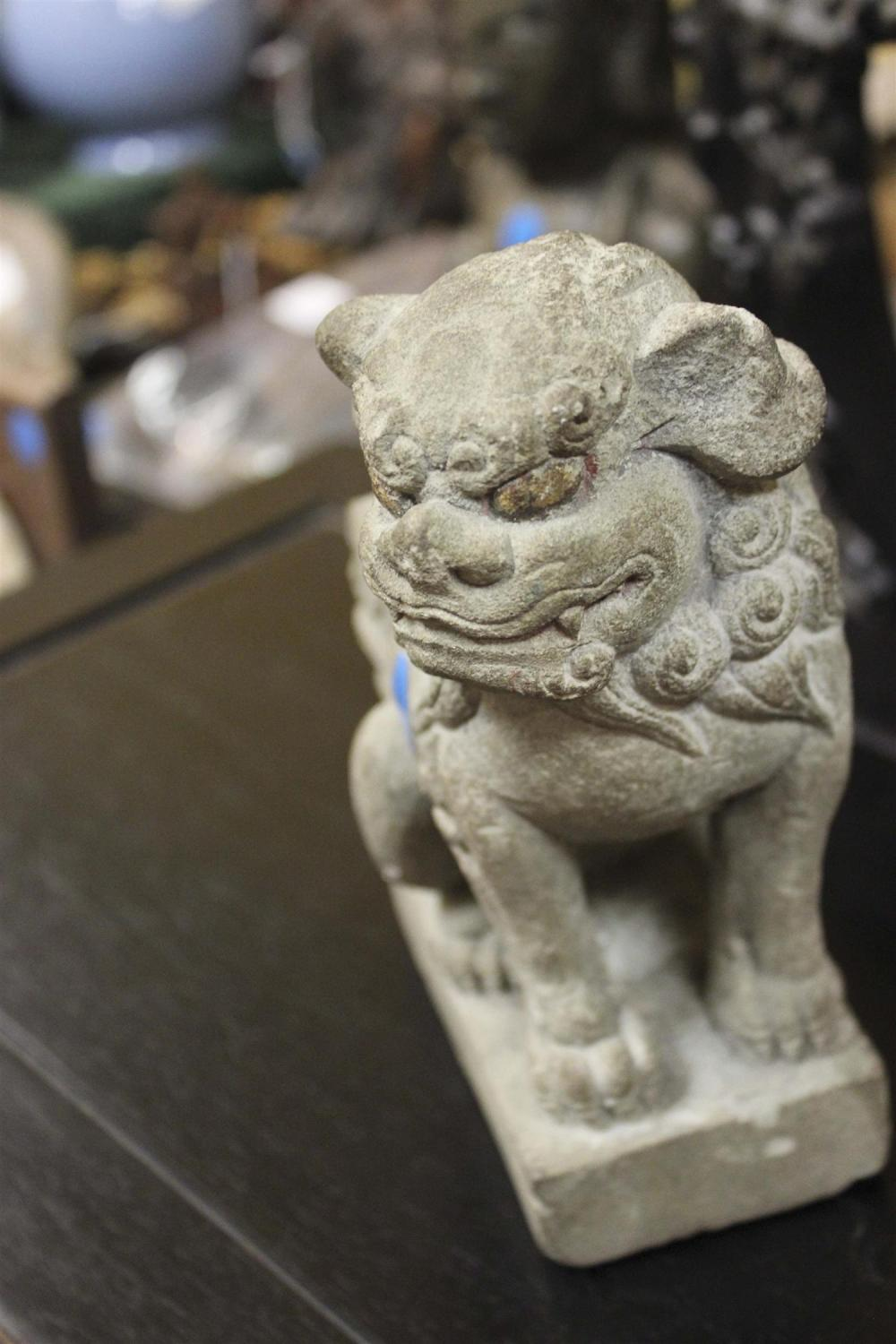 CHINESE SANDSTONE FIGURE OF A FU DOG Seated on a rectangular plinth. Traces of gilding to eyes. Height 7.5