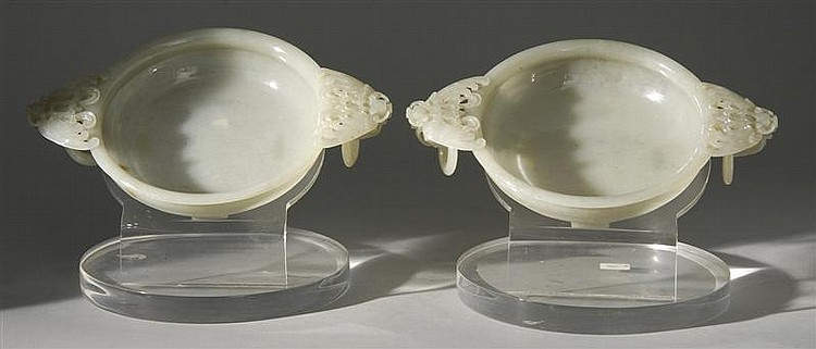 PAIR OF WHITE JADE BOWLS With four-footed bases, bat and loose ring handles, and concentric ring design on body. Lengths 9