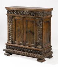 WALNUT CUPBOARD With molded top and floral-carved pilasters. Two drawers, two doors, and bracket base. Height 38.5