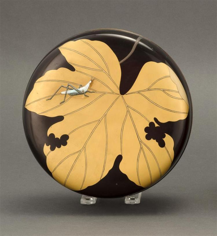 BLACK AND GOLD LACQUER CIRCULAR BOX Cover decorated with a grasshopper on a large leaf. Interior with prunus blossom and brocade des...