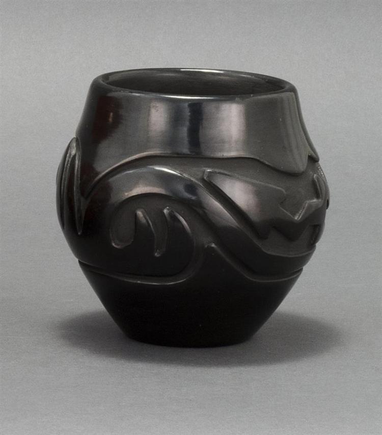 SANTA CLARA PUEBLO BLACK-ON-BLACK POTTERY JAR By Stella Tafoya Chavarria (b. 1939). In globular form with serpent design. Diameter 5...
