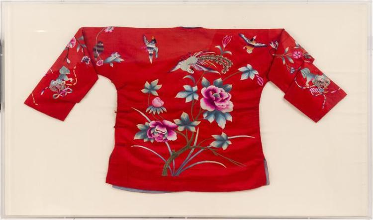 EMBROIDERED CHILD'S JACKET Depicting an exotic bird and peonies on red silk ground. Framed 30.5