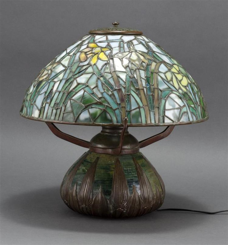 TIFFANY-STYLE LEADED GLASS TABLE LAMP Jonquil pattern shade numbered 1449. Mosaic and bronze base with leaf design signed