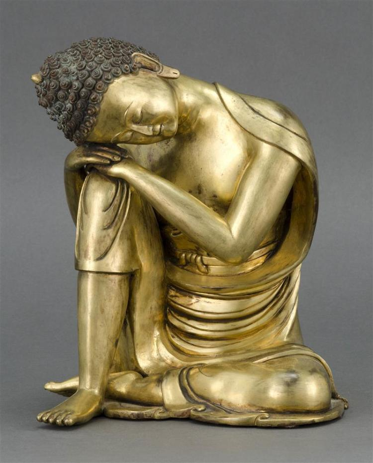 SINO-TIBETAN GILT-BRONZE FIGURE OF BUDDHA Depicted in an unusual sleeping posture with head resting on raised right knee. Height 9.5