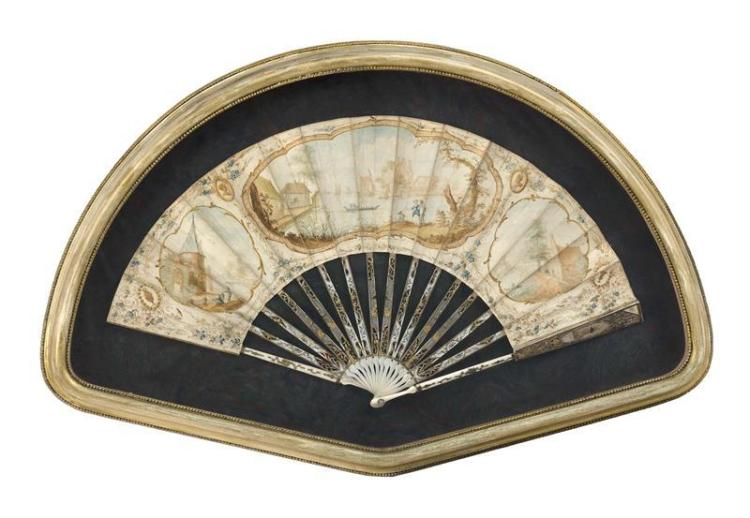 BONE AND PAINTED PAPER FAN With three Watteau-style landscape cartouches. Carved and gilded sticks and guards. Length 20.5
