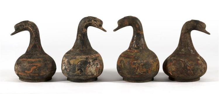 SET OF FOUR POTTERY WATER BOTTLES In goose form with ovoid bodies. Traces of original polychroming. Heights 14.5