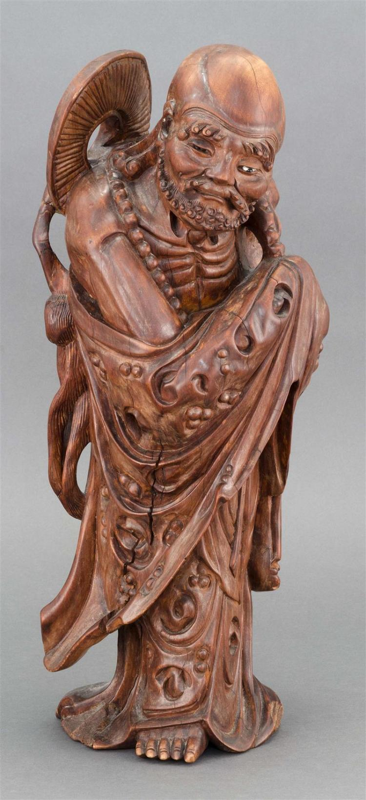 CARVED WOOD FIGURE OF AN IMMORTAL In standing position carrying his hat on his back. Glass eyes. Height 19.25
