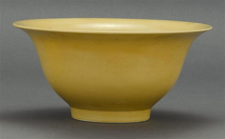 YELLOW GLAZE PORCELAIN BOWL In bell form with two drainage holes in base. Six-character Kangxi mark incised on base. Diameter 9