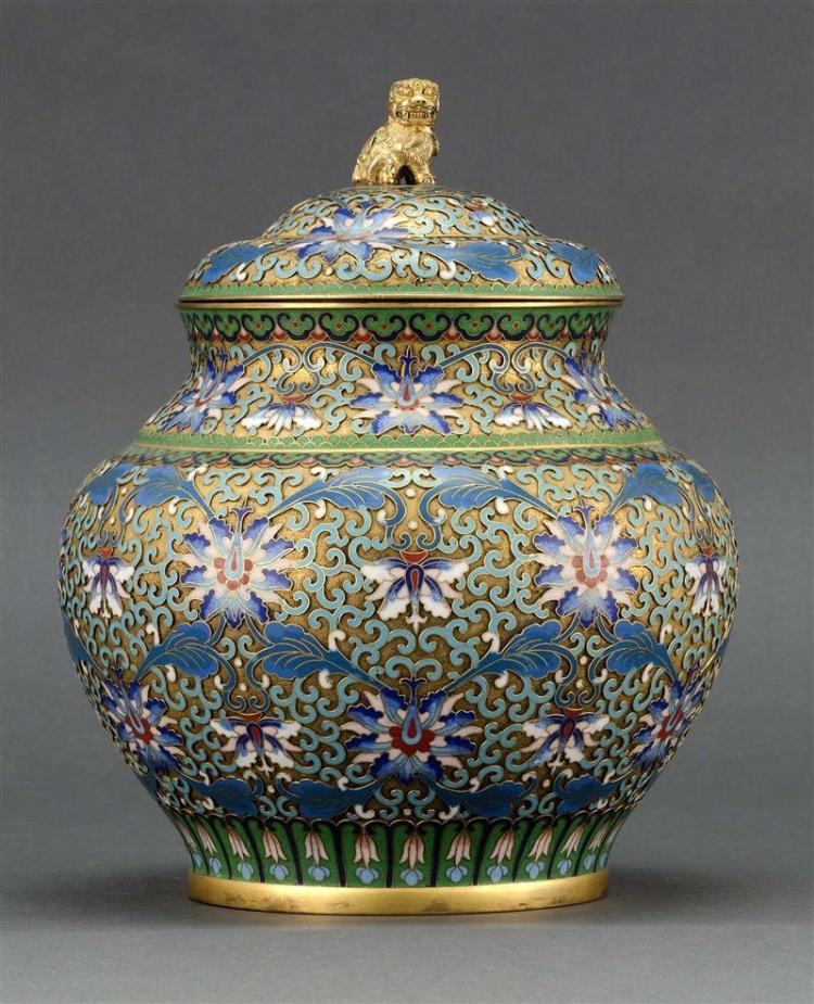 CLOISONNÉ ENAMEL COVERED JAR In ovoid form with relief passionflower design on a gilt ground. Domed cover with lion finial. Height 9...