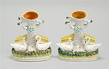 PAIR OF STAFFORDSHIRE VASES In the form of trees with swans at base. Heights 5.75
