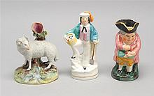 THREE STAFFORDSHIRE ITEMS A tree-form vase with sheep at base, a male figure with shovel and basket, and a small Toby jug. Heights f...