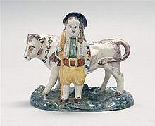 FAÏENCE FIGURE GROUP Depicting a farmer and cow. Length 5.25