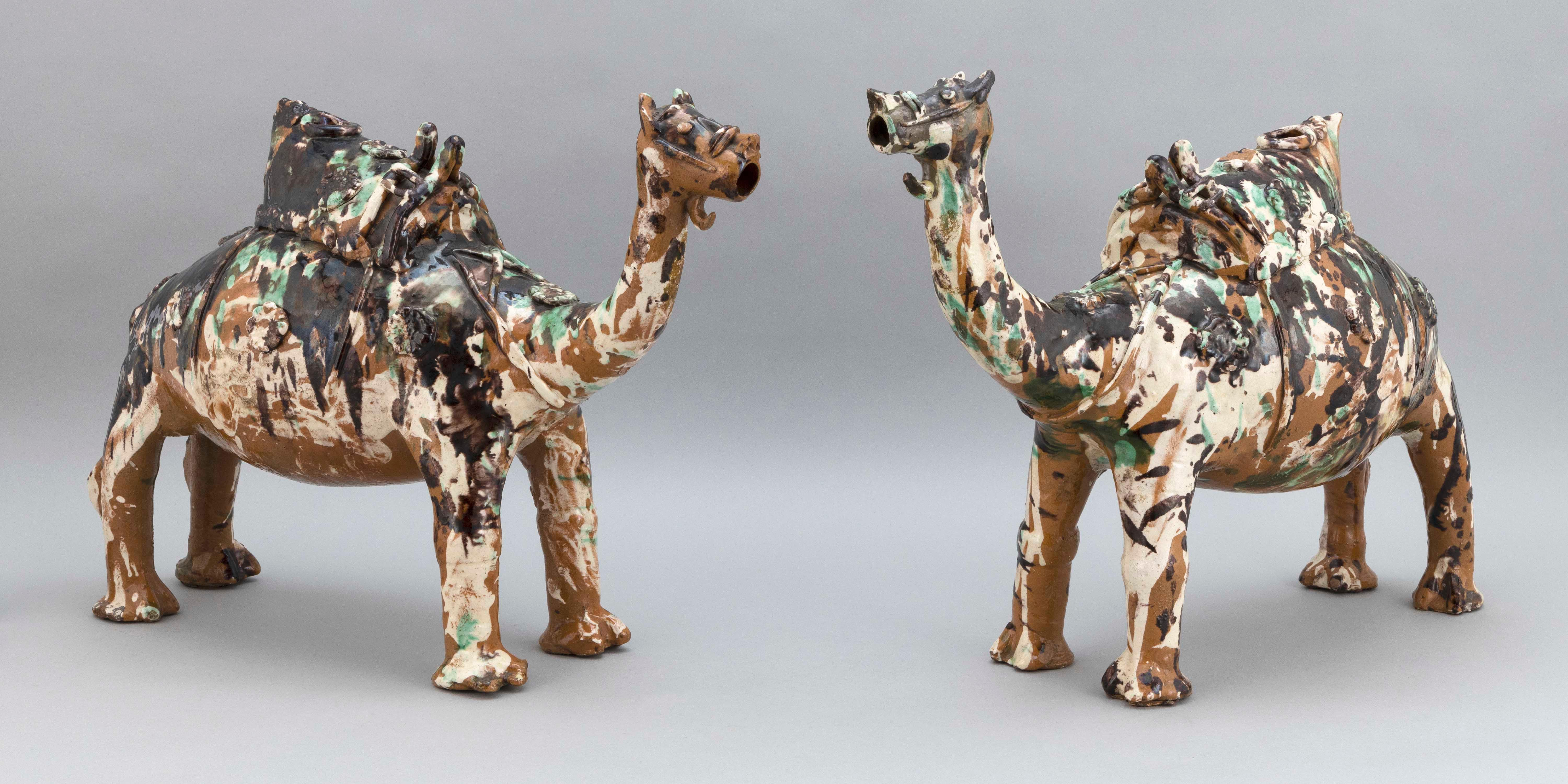 """PAIR OF CHINESE SANCAI POTTERY CAPARISONED CAMEL-FORM WINE JARS Late 19th Century Heights 15"""". Lengths 19"""". Widths 8""""."""