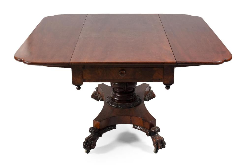 CLASSICAL ONE-DRAWER DROP-LEAF TABLE In mahogany and mahogany veneer. Carved pedestal raised on lion's-paw feet fitted with brass ca..