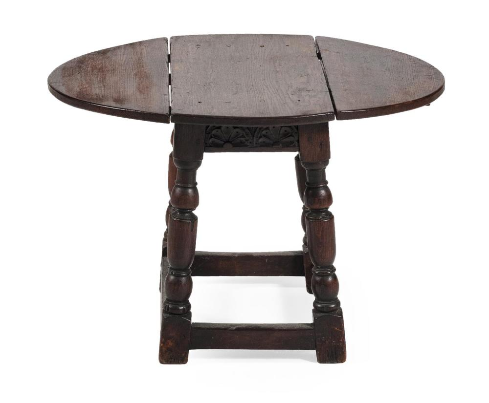 ENGLISH DROP-LEAF STAND In oak, with oval top, turned legs and stretcher base. Height 18