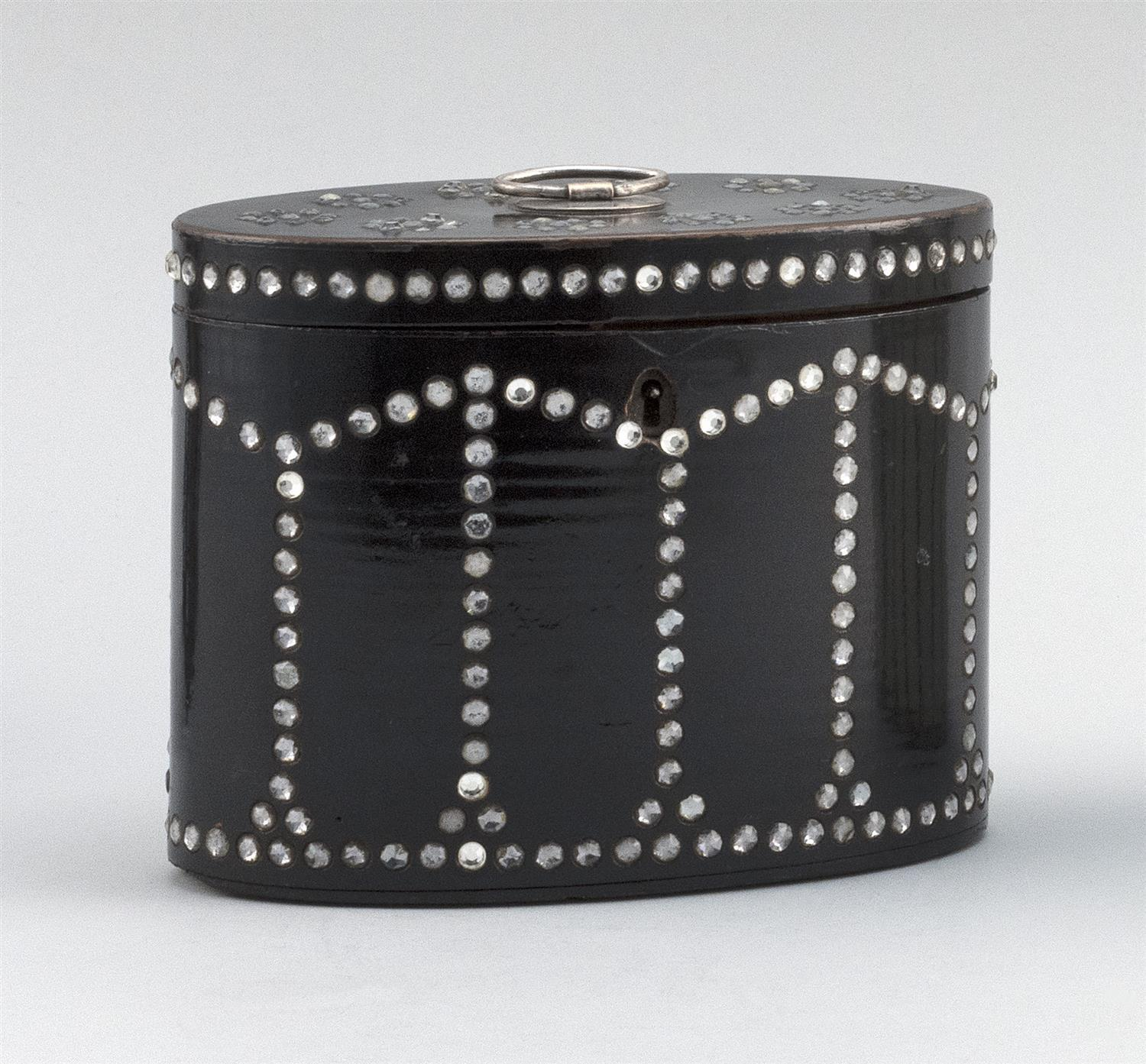 """ENGLISH BLACK LACQUER OVAL TEA CADDY Inset with glass beads in a geometric design. Lift top and fitted interior. Height 5"""". Width 6""""..."""