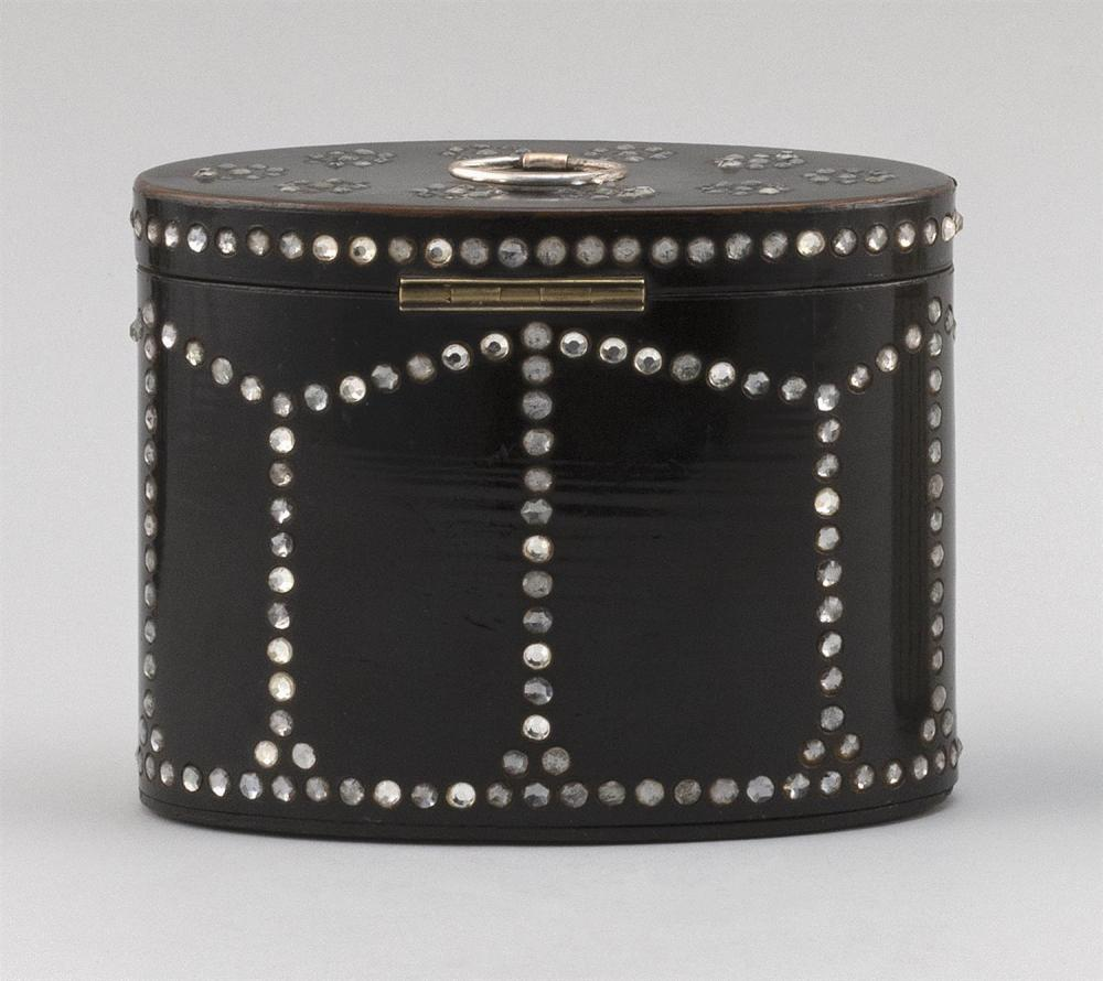 ENGLISH BLACK LACQUER OVAL TEA CADDY Inset with glass beads in a geometric design. Lift top and fitted interior. Height 5