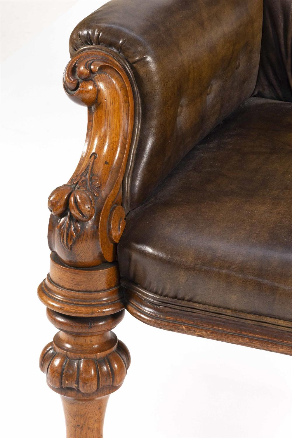 FINELY CARVED ENGLISH GENTLEMAN'S CHAIR In oak, with brown faux leather upholstery. Arms heavily carved in a fruiting vine design. B..