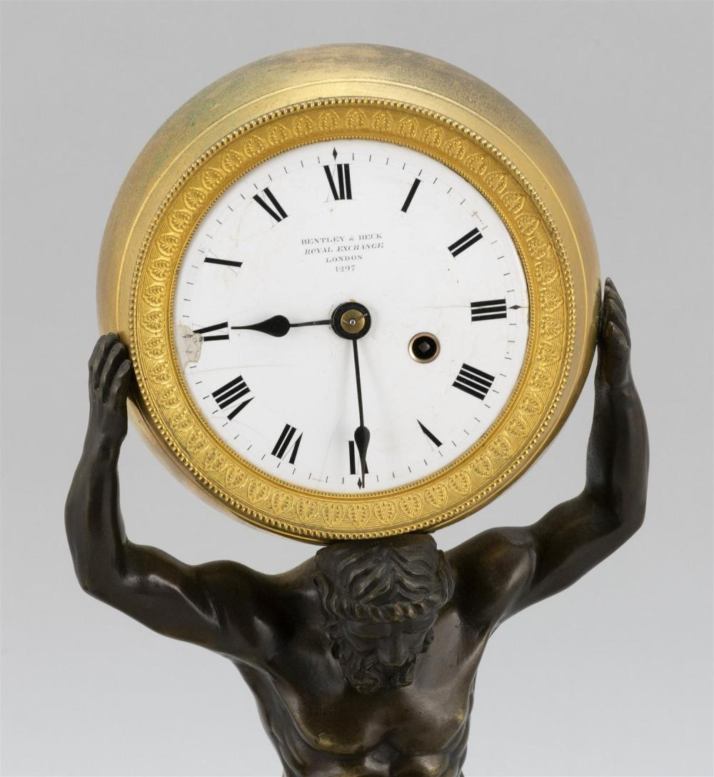 NEOCLASSICAL FIGURAL PARCEL-GILT BRONZE MANTEL CLOCK Base possibly French, cast as a kneeling Atlas holding the globular clock case....