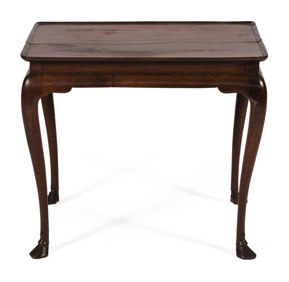 IRISH QUEEN ANNE TRAY-TOP TEA TABLE In mahogany, with molded-edge top and cabriole legs ending in hooved feet. Height 26