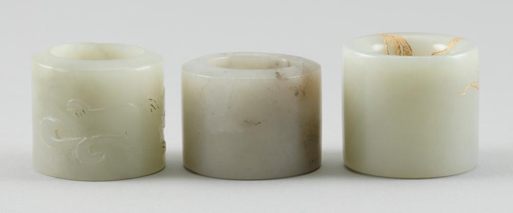 THREE CELADON JADE THUMB RINGS