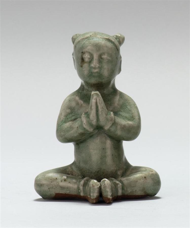 "CELADON PORCELAIN FIGURE In the form of a child Buddha seated in a prayerful posture. Height 4.75"" (12 cm)."