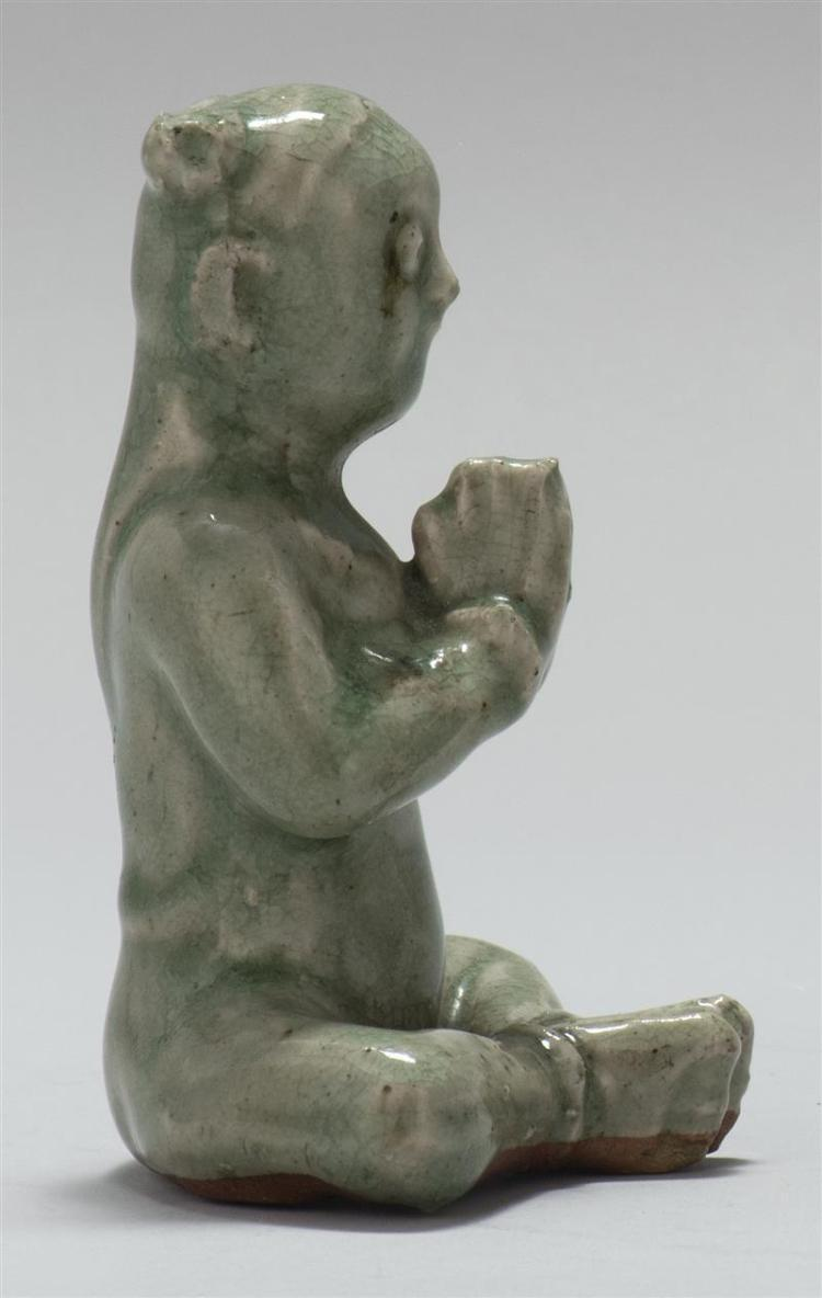 CELADON PORCELAIN FIGURE In the form of a child Buddha seated in a prayerful posture. Height 4.75