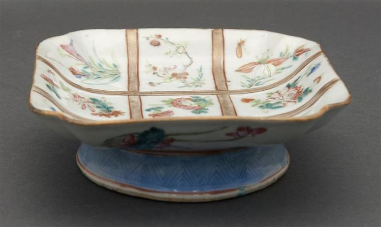 FAMILLE ROSE PORCELAIN CUT-CORNER TAZZA In square form with nine floral sprays highlighted by gilt latticework. Blue rain design at...