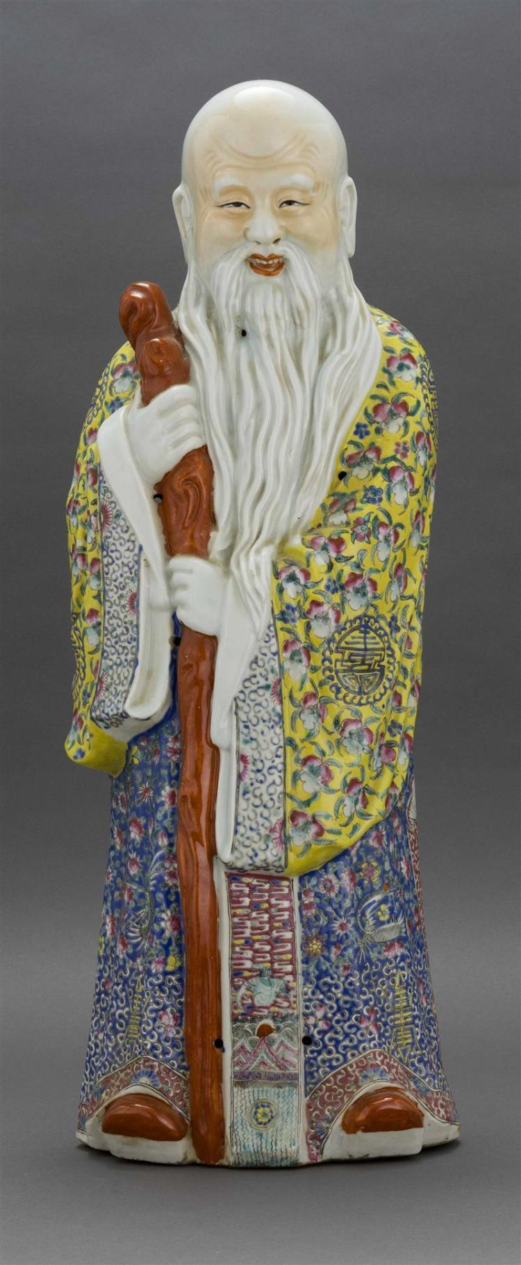 POLYCHROME PORCELAIN FIGURE OF SHOULAO In standing position holding a tree branch staff and dressed in a yellow robe with a blue ski...