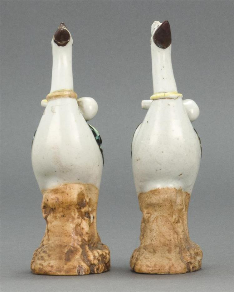 PAIR OF BISQUE AND POLYCHROME PORCELAIN BIRD FIGURES Perched on rockery bases with double gourd vases at their necks. Heights 6.3