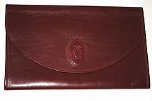 CARTIER - pochette en cuir bordeaux avec rabat, 27x 17 cm, boîte cadeau et sac f