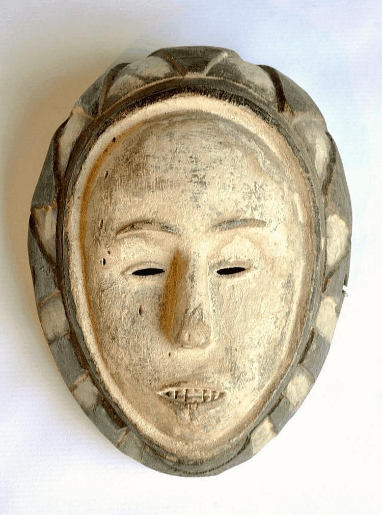 Gabon (Région des estuaires), FANG ou BETSI. FANG ou BETSI. Nord Gabon (Région des estuaires). Petit masque ovale ngontang (La jeune femme blanche) de danse bicolore dont le visage est traité au kaolin. La facture très sobre confère à ce masque une