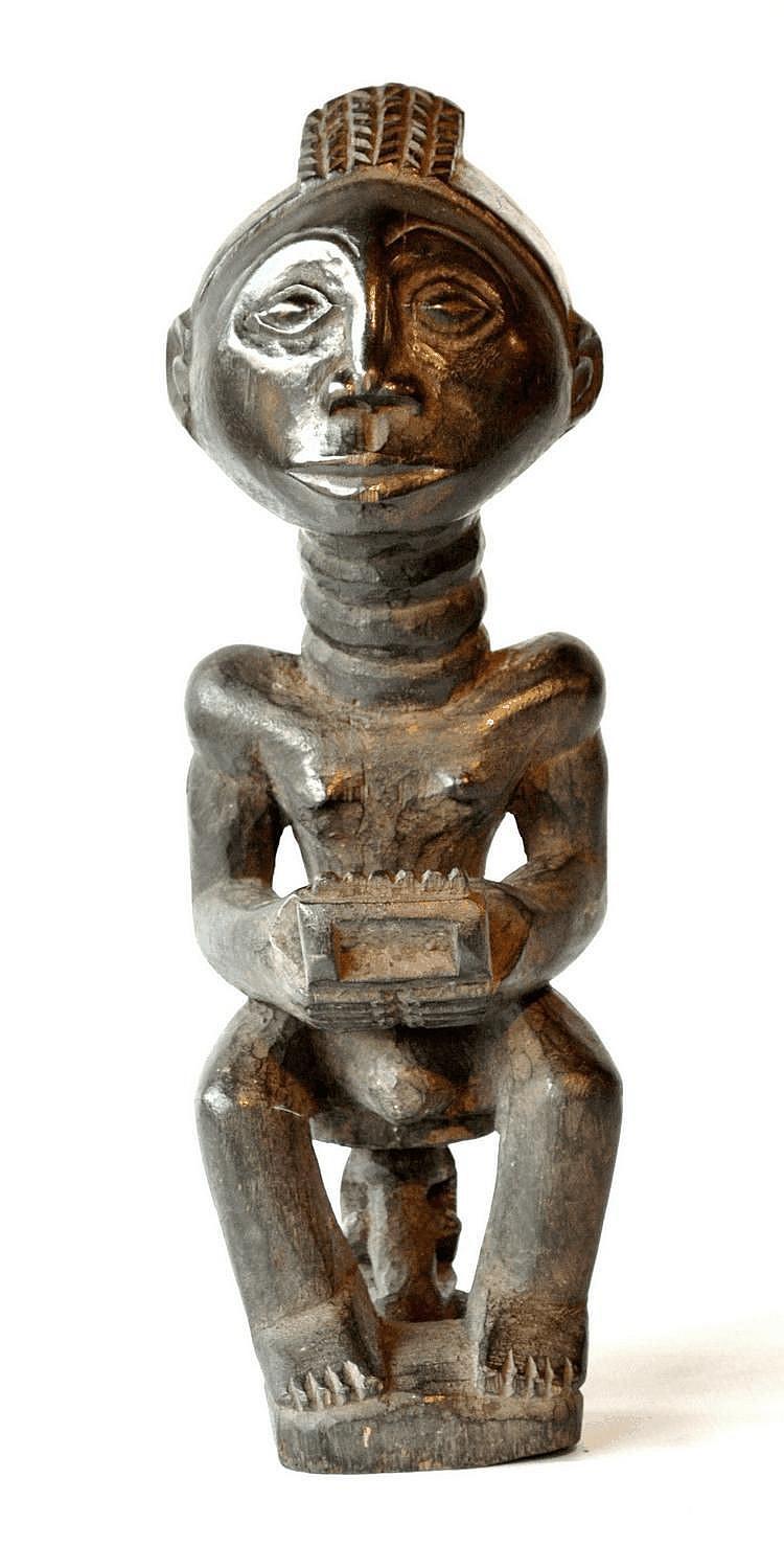RDC,  KUBA. Sculpture représentant un musicien assis sur petit un tabouret.  Il tient dans les mains un xylophone. La coiffe est surmontée d'un fort joli motif en escalier. Belle patine ancienne. Bois 35,2 cm