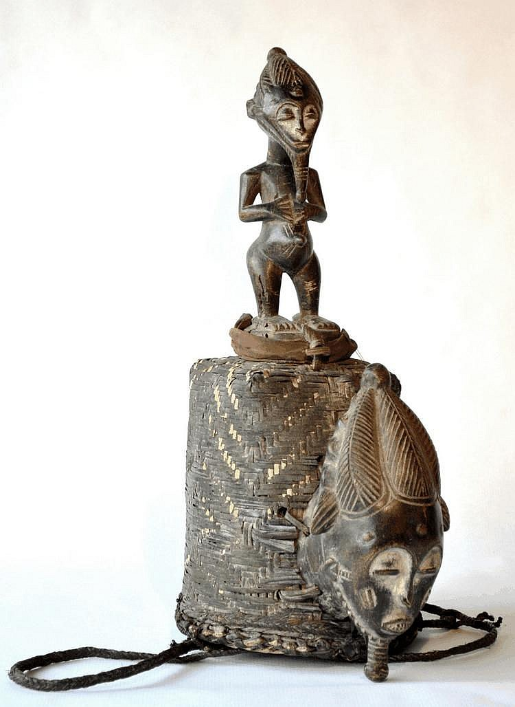 Côte d'Ivoire, BAOULE. Rare coiffe d'initié se présentant sous la forme d'un chapeau surmonté d'une sculpture masculine se tenant debout les mains posées sur l'abdomen. Accroché au chapeau une masquette représentant une tête d'homme orne l'ensemble