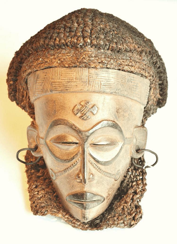RDC, TCHOKWE. Élégant masque de danse à visage féminin Pwo. La coiffe d'origine accompagne le masque. La bouche est particulièrement bien dessinée et l'ensemble des scarifications confère à ce masque une «beauté sereine» propre à l'ethnie Tchokwe.
