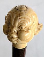 CANNE à pommeau en ivoire sculpté d'une tête soufflant un scarabée sur la tête,