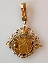 PENDENTIF en or jaune, la bélière à décor de rosace, la monture à enroulements r