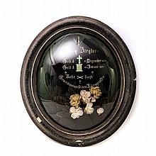 Großes Andenkenbild, Anfang 20. Jh. - Ovales Gedenkbild im Holzrahmen hinter Glas mit eingelegtem künstlichen Blumenschmuck,